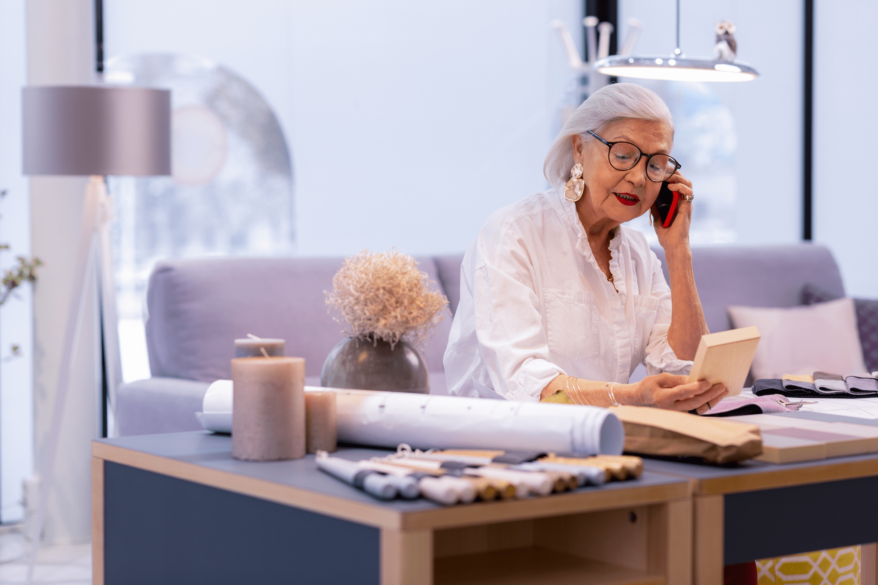 Sophisticated older woman takes a call while looking at her calendar