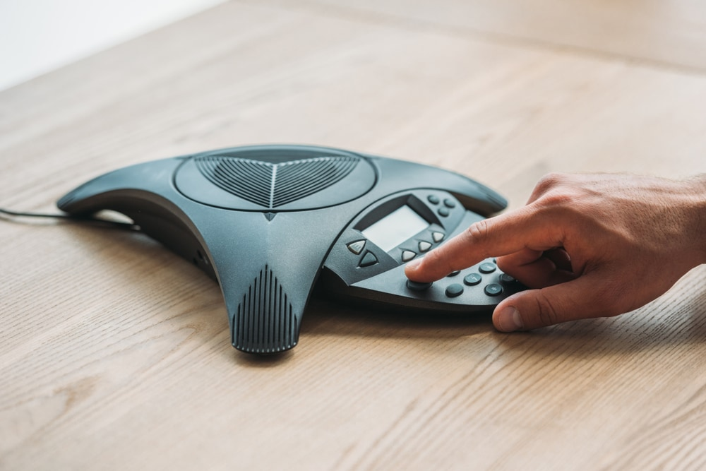 A-hand-dialing-a-conference-speakerphone-set-in-the-center-of-a-conference-table
