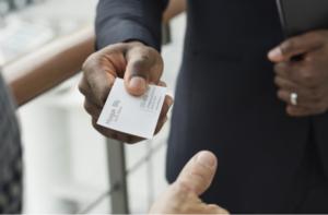 Businessman hands his client a business card
