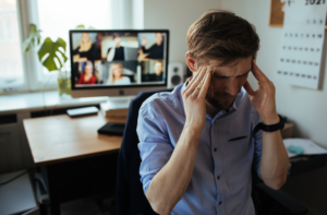 Man experiences Zoom fatigue and turns away from a video conference with hands on his head